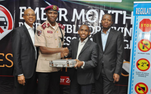 """MD/CEO, Guinness Nigeria, Peter Ndegwa (2nd Right) hands over a set of breathalyser to the Lagos Sector Commander, Federal Road Safety Commission, Mr. Hyginius Omeje, with Head of Policy and Public Affairs, Michael Onuoha, and Corporate Relations Director, Sesan Sobowale both of Guinness Nigeria at the flagoff of the """"Ember Months Responsible Drinking Awareness Campaign"""" in Lagos"""